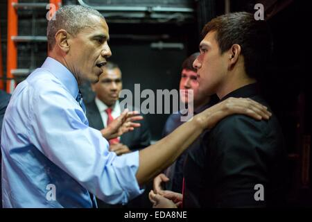 US President Barack Obama talks with two young men who heckled him during a speech on the economy July 10, 2014 - Stock Photo