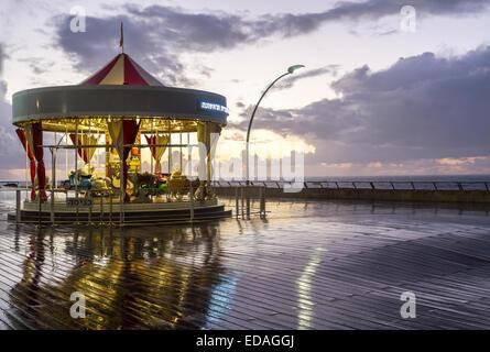 Tel-Aviv , Israel - December 20 . 2014 : Illuminated retro carousel on the seafront at sunset in the rain. Port - Stock Photo