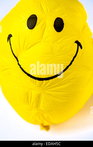 old Balloon, yellow, shriveled with friendly smiley face,  sunken, wrinkled