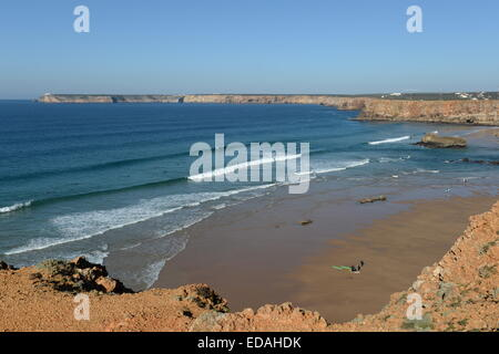 perfect  surfing conditions at  Tonel Beach Sagres with Cape St. Vincent lighthouse in background - Stock Photo