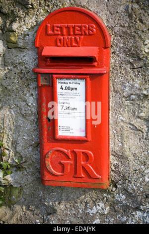 Red post box in stone wall - Stock Photo