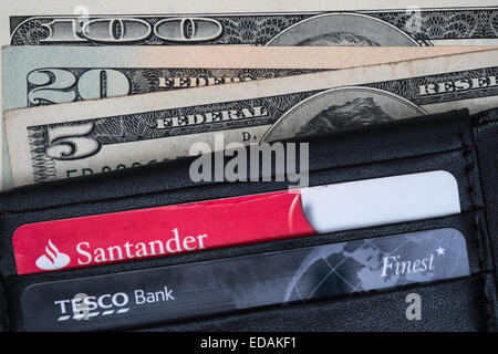Wallet containing Santander and Tesco bank cards, and american dollars. - Stock Photo