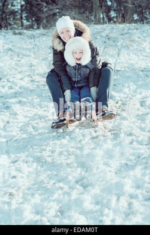 young beautiful mother and her little son on the sledge - Stock Photo