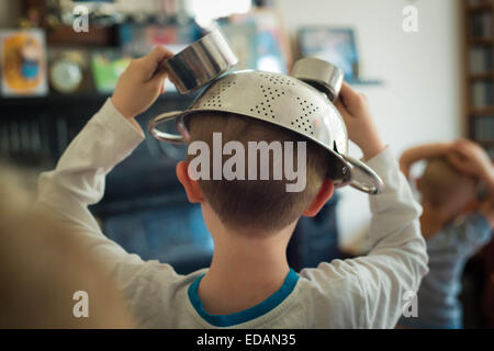 Boy playing games with metal colander on head - Stock Photo