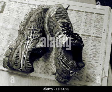 Dirty Muddy Training shoes on a newspaper protecting the floor - Stock Photo