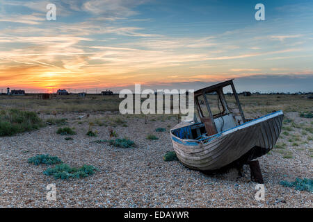 An old wooden fishing boat stranded on shingle in Kent under a dramatic sunset sky - Stock Photo