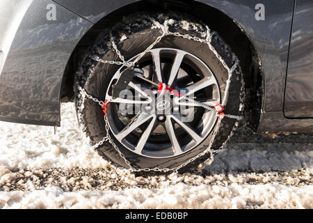 Snow chain / chains on front wheel / wheels of a car also fitted with winter tyres / tires. (75) - Stock Photo