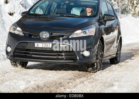 Woman driver driving a car fitted with snow chain / chains on front wheel / wheels and winter tyres / tires. - Stock Photo