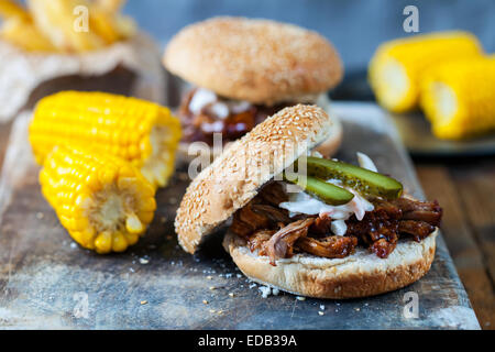 Burger with pulled pork, sweetcorn and chips - Stock Photo