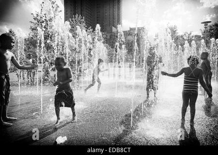Kids Playing in a Fountain on a Hot Summer Day, Baltimore, Inner Harbor, Maryland, USA - Stock Photo