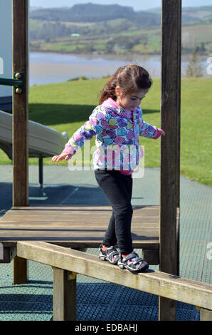 Little child (girl age 04) walks on a balance board in the playground. - Stock Photo