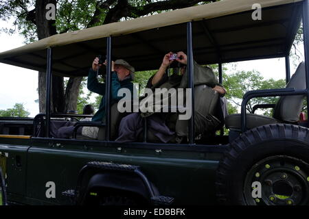 Tourists photograph birds from a game drive vehicle whilst on safari in Botswana - Stock Photo