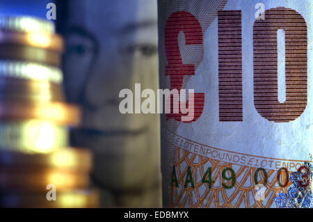 Close-up picture of ten pound notes and a stack of Britsh sterling coins. - Stock Photo
