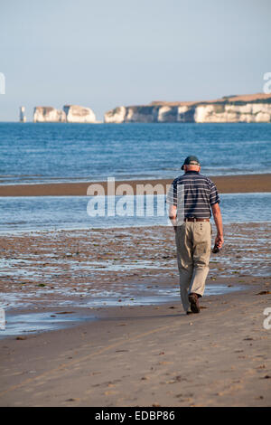 Man holding camera walking along beach at Studland with Old Harry rocks out of focus in the distance on a July evening - Stock Photo