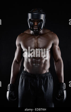 Portrait of African American boxer wearing protective gear standing on black background. Muscular young man in boxing - Stock Photo