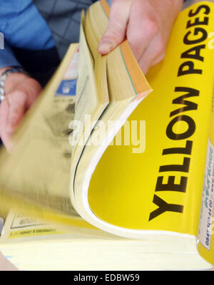 A man using the Yellow Pages telephone Directory - Stock Photo