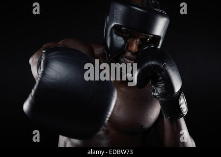 Portrait of African male practicing boxing looking at camera against black background. Male boxer throwing a punch - Stock Photo