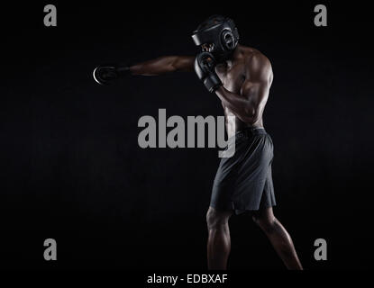 Side view of muscular man boxing on black background. Afro American young male boxer practicing shadow boxing. - Stock Photo