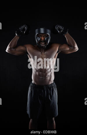 Portrait of happy young African boxing winner on black background. Muscular male boxer celebrating his win with - Stock Photo