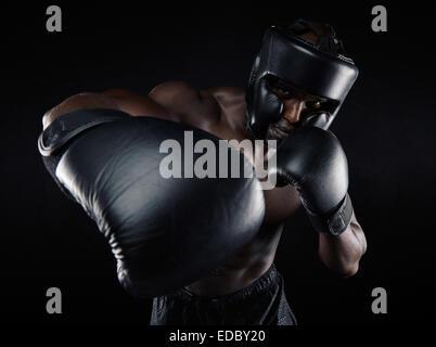Portrait of young male practicing boxing against black background. African Male boxer throwing a punch in front. - Stock Photo