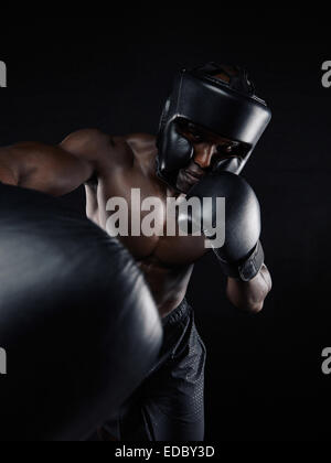 Portrait of a young man boxer throwing a punch at camera while practicing on black background. Male athlete wearing - Stock Photo