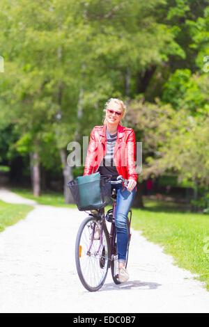 Young woman riding a bicycle. - Stock Photo