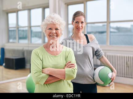 Portrait of happy senior woman standing with her arms crossed and her personal trainer in background gym. Fitness - Stock Photo