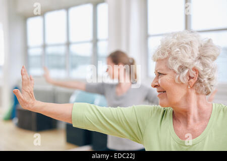 Indoor shot of senior woman doing stretching exercise at yoga class. Women practicing yoga at gym. - Stock Photo