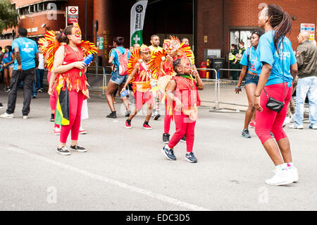 LONDON, UK- August 24th 2014: Notting Hill Carnival, Children's Day. Group of kids dancing as part of the parade. - Stock Photo