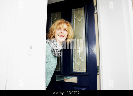 Woman looking out of her front door to greet visitors - Stock Photo
