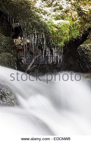 Whitewater running under icicles - Stock Photo