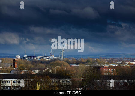 Manchester Etihad Stadium on the skyline with a Virgin train passing - Stock Photo