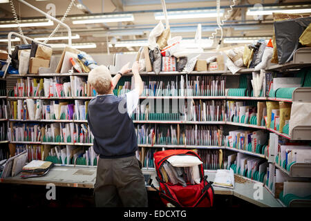 Royal Mail Manchester South delivery office workers sorting the mail by hand - Stock Photo