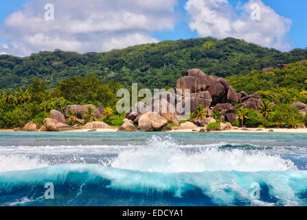 Big waves in front of granite rocks and a hill on island la Digue, Seychelles. Beach - Anse source d' Argent. - Stock Photo