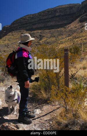 My senior sister and her dog at the 1.5 mile marker along trail in Oliver Lee State Park New Mexico - USA - Stock Photo