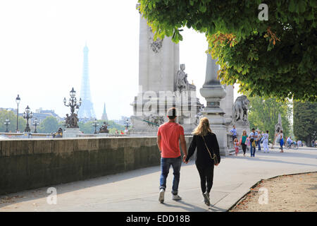 Couple walking towards the Pont Alexandre III bridge in Paris, in Autumn, the Eiffel Tower behind, France, Europe - Stock Photo