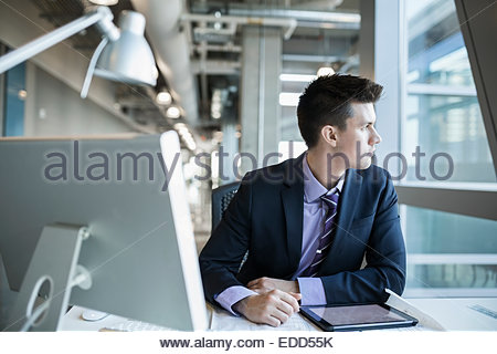 Pensive businessman looking out window - Stock Photo