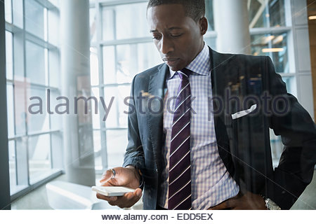 Businessman texting on cell phone in lobby - Stock Photo
