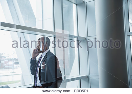 Businessman talking on cell phone at window - Stock Photo