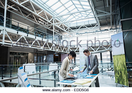 Businessman checking in at conference registration table - Stock Photo