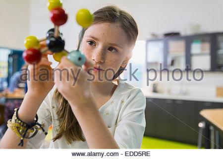 Elementary student examining molecule model - Stock Photo
