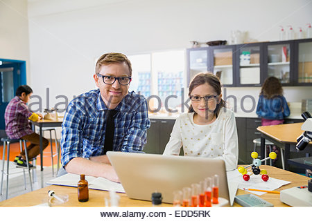 Portrait of teacher and elementary student in laboratory - Stock Photo