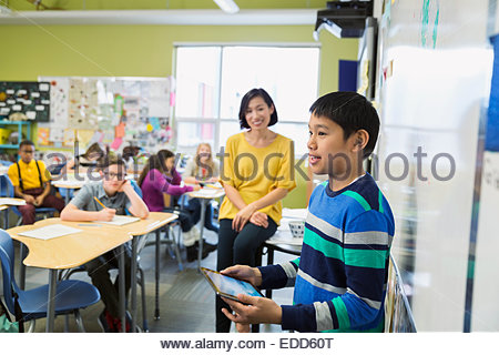 Student with digital tablet in front of classmates - Stock Photo
