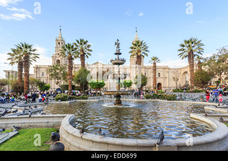 View of a fountain in the famous Plaza de Armas, town square in Arequipa, Peru with the iconic Arequipa Cathedral - Stock Photo
