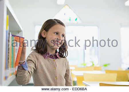 Smiling elementary student selecting book in library - Stock Photo