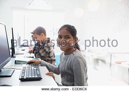 Elementary students using computers in classroom - Stock Photo