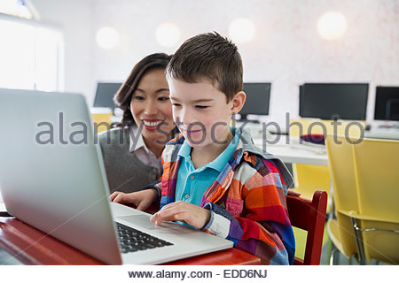 Teacher and elementary student using laptop in classroom - Stock Photo