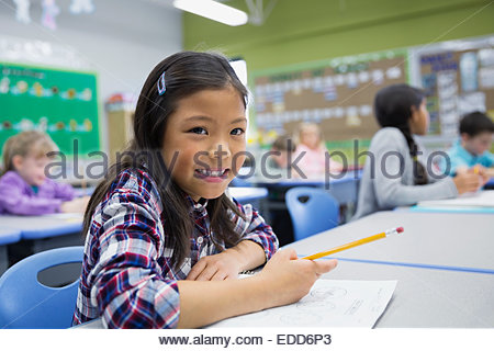 Portrait of smiling elementary student at desk - Stock Photo
