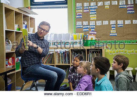 Elementary students listening to teacher read in classroom - Stock Photo