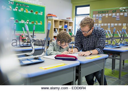 Teacher helping elementary student in classroom - Stock Photo